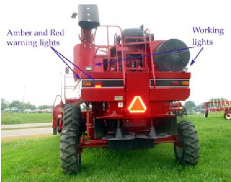 Photo 3: This combine shows a good SMV, amber and red retroreflective tape, and red and amber lights. Not visible are headlights. The working lights should not be used when traveling on public roadways.