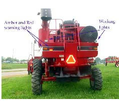 Photo 2: The combine utilizes a good SMV, amber and red retro reflective tape, and red and amber lights. Not visible are headlights. The working lights should not be used when traveling on public roadways.