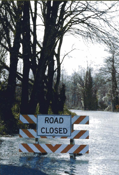 Photo of a barrier Road Closed sign in a flood