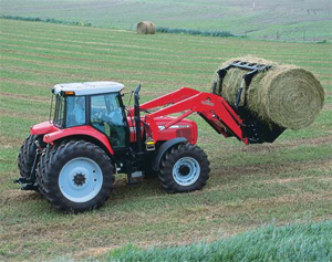 Photo of a red tractor carrying a round hay bale
