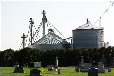 Photo of a cemetary in front of grain bins