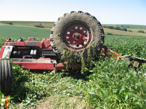 An upside-down tractor in a field