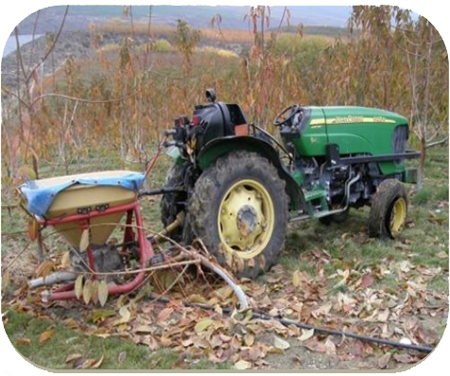Photo of tractor with spreader.